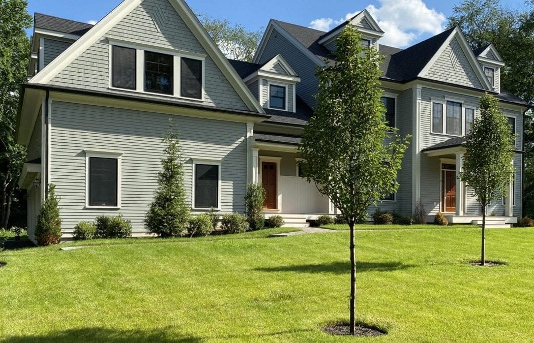Pictured is an after picture of a recent landscape design project. There is green grass, trees and shrubs!
