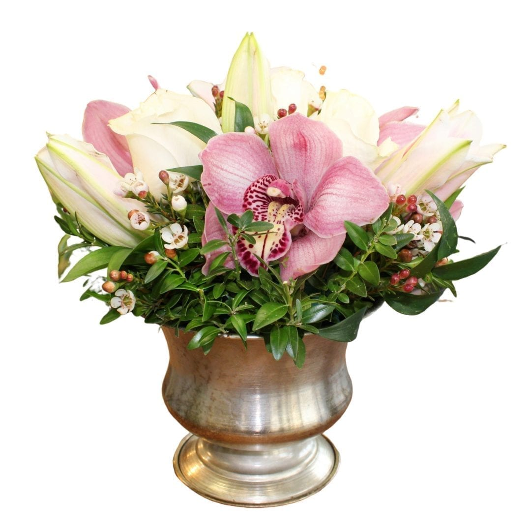 Pictured is a floral arrangement with white and pink flowers and well as greens! It is siting in a silver vase created by our florist!