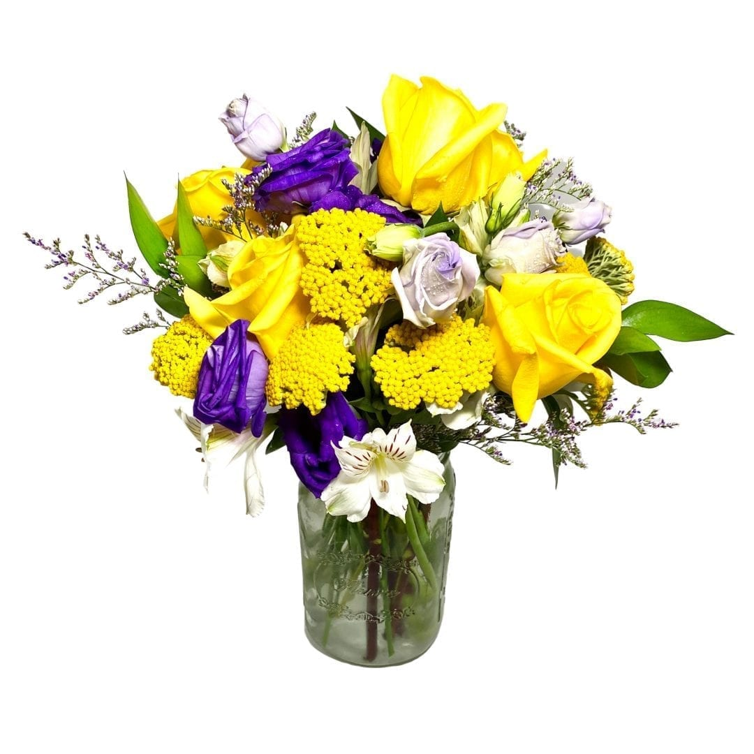 Pictured is a floral arrangement with yellow, blue and white flowers! It instating in a clear vase created by our florist!