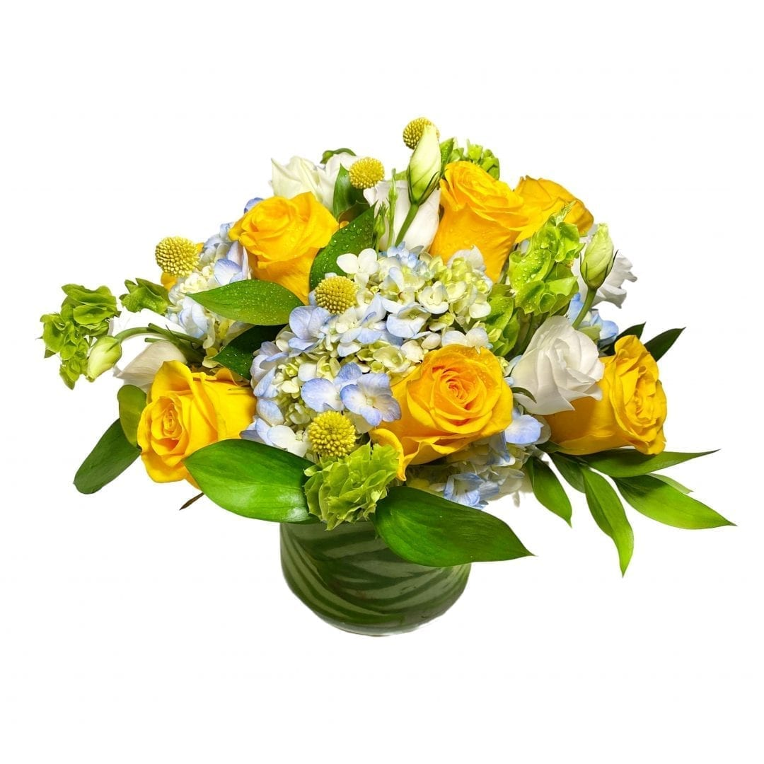 Pictured is a floral arrangement with yellow, blue and white flowers created by our florist.