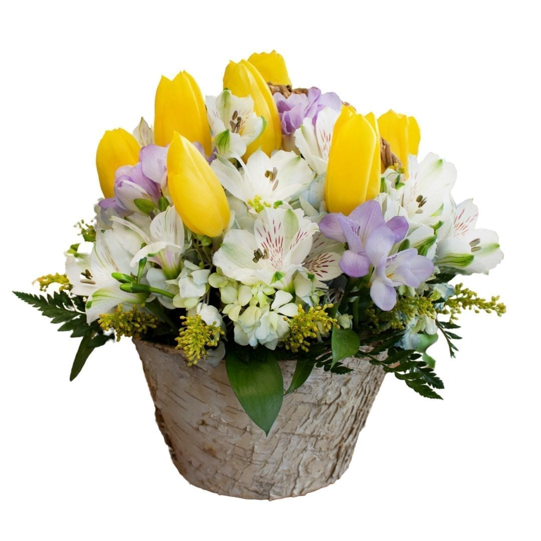 Pictured is a floral arrangement with yellow, white and pink flowers! It is siting in a pot made of white wood created by our florist!
