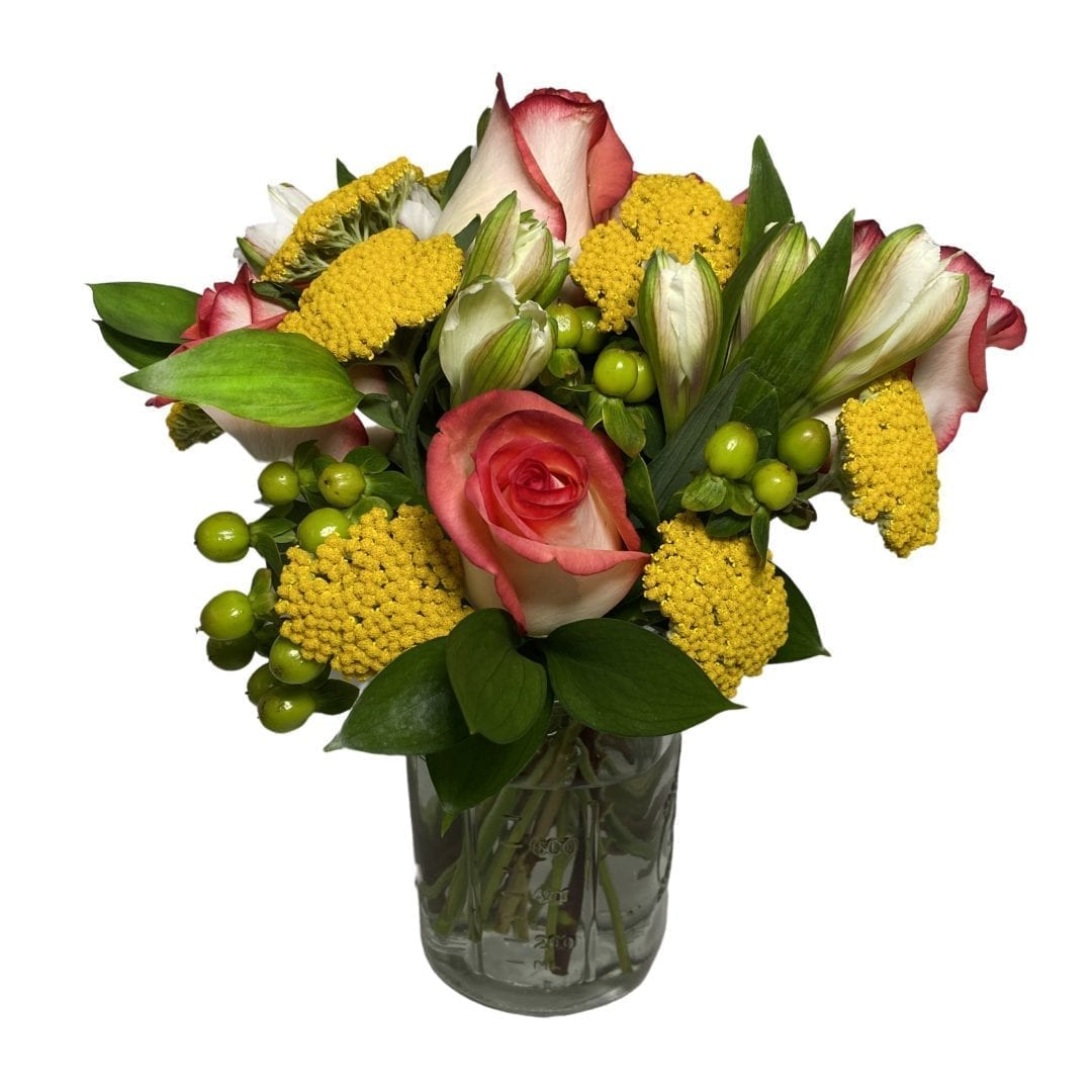 Pictured is a floral arrangement with yellow and red flowers! It is sitting in a red clear vase created by our florist!