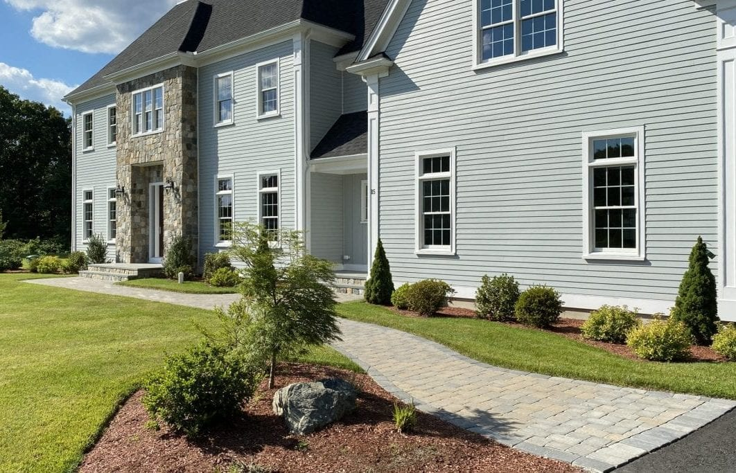 Pictured is the front yard of a home we recently landscape designed. There is green grass, shrubs and trees!