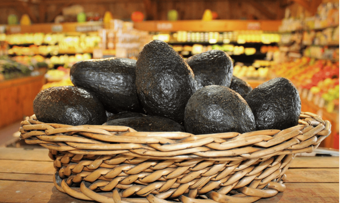 Pictured is a basket filled with avocados in front of our farm stand produce!