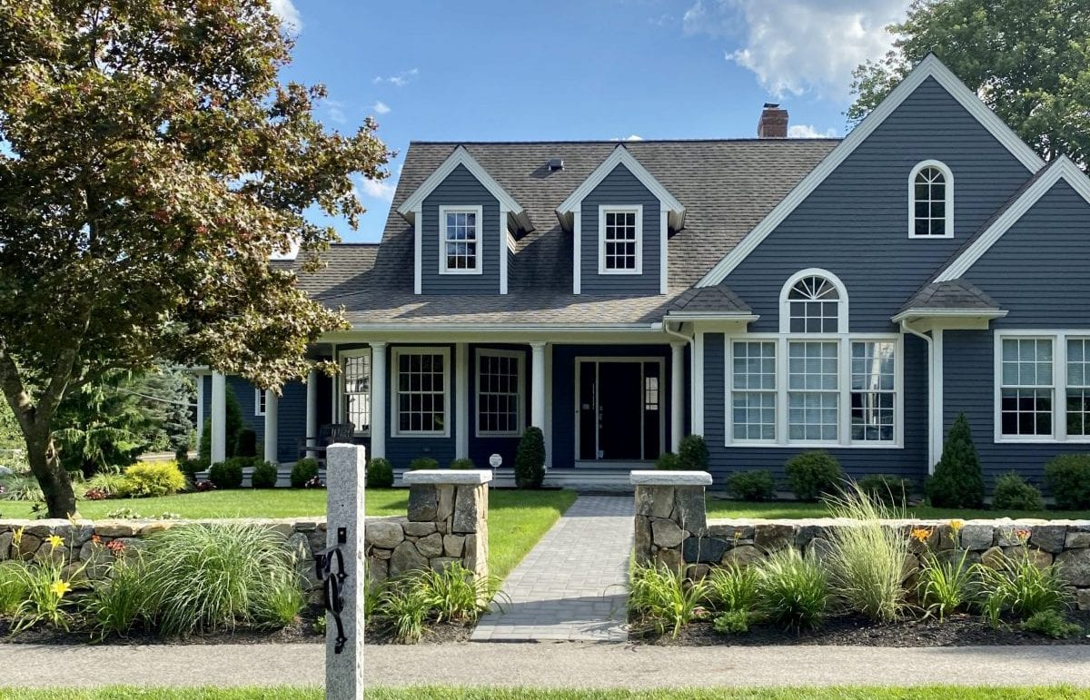 A recently landscaped front yard of a home with trees, shrubs and decorative grasses.