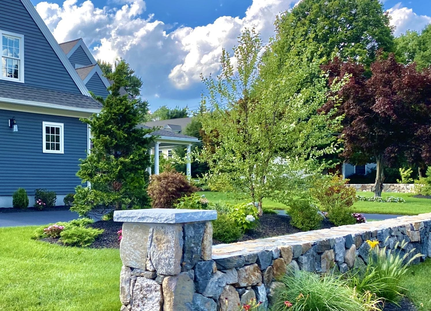 The side yard of a home that we recently landscape designed with trees and shrubs. There are rock walls surrounding the yard.
