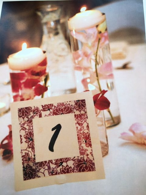 White and red flowers sit inside glass candle holders with a matching table number card sitting in front of them.
