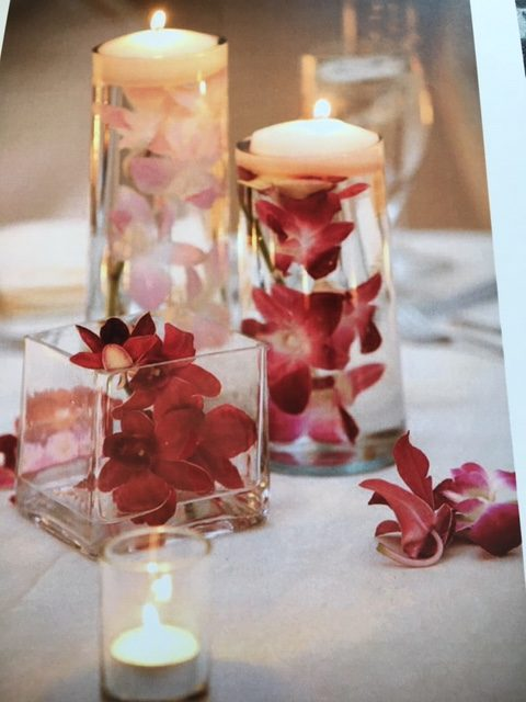 White and red flowers sit inside decorative glass candle holders.