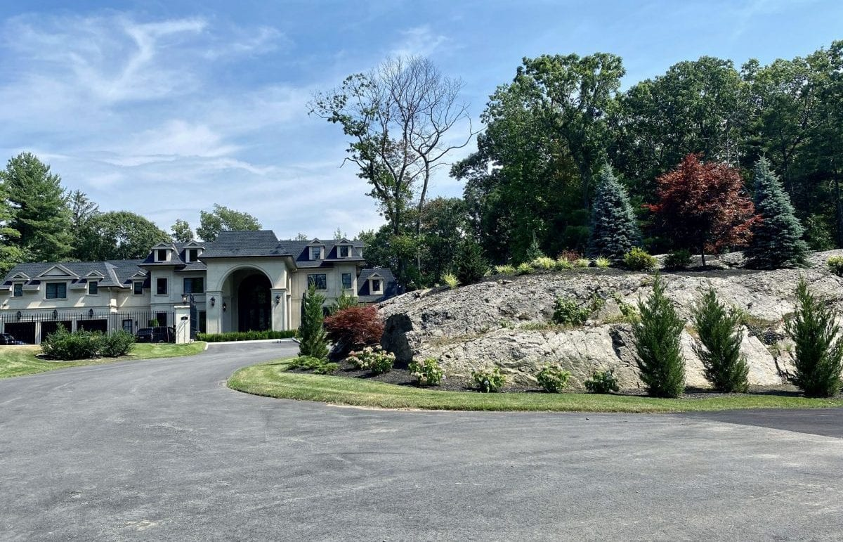 An after picture of a cul de sac that we recently landscape designed with trees and shrubs on top of it.