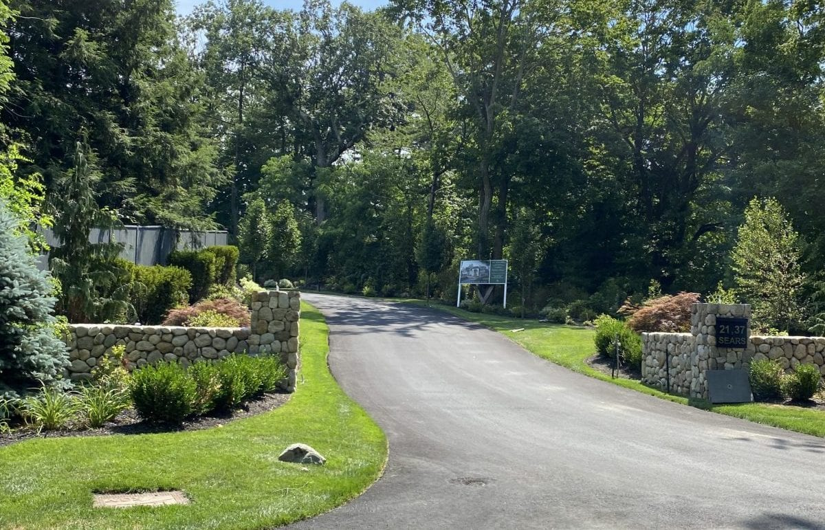 An after picture of a residential road that we recently landscape designed. There is green grass with trees and shrubs, as well as rock walls.