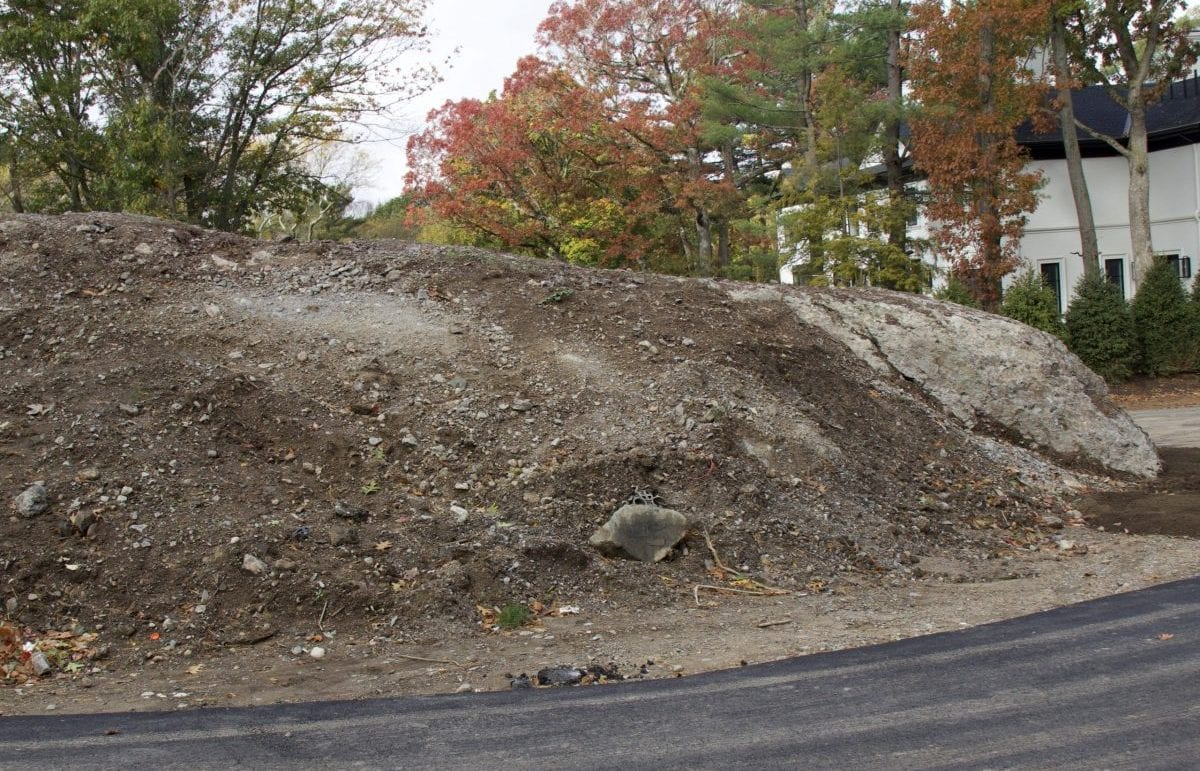 A before picture of a the median of a road that we recently landscape designed. It is covered in bare dirt.