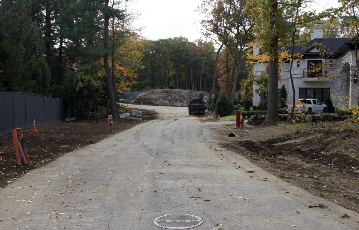 A before picture of a residential road that we recently landscape designed with bare dirt along the sides of the road.