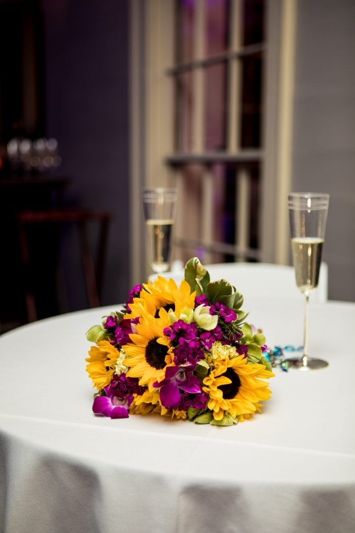 Decorative wedding floral arrangement with pink flowers and yellow sunflowers created by our florist!