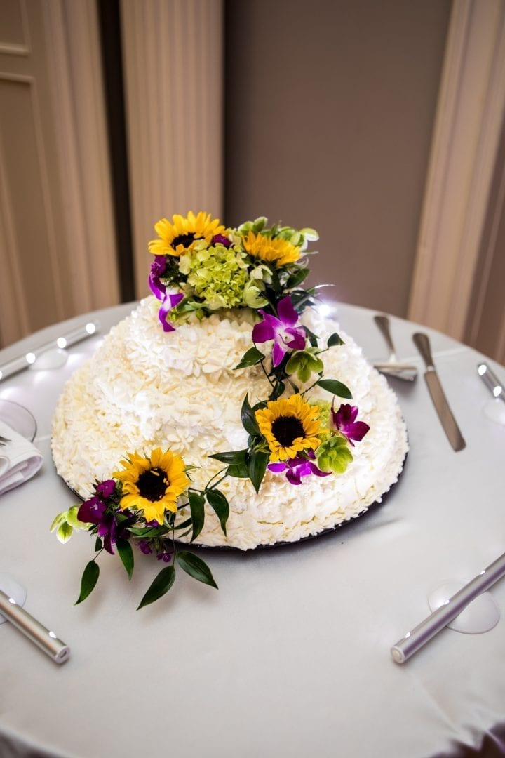 Yellow and blue floral arrangement created by our florist on a wedding cake.