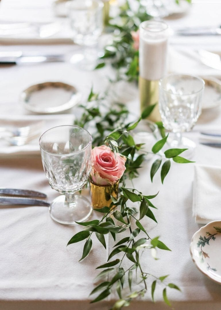 A green garland sits atop a long wedding table.