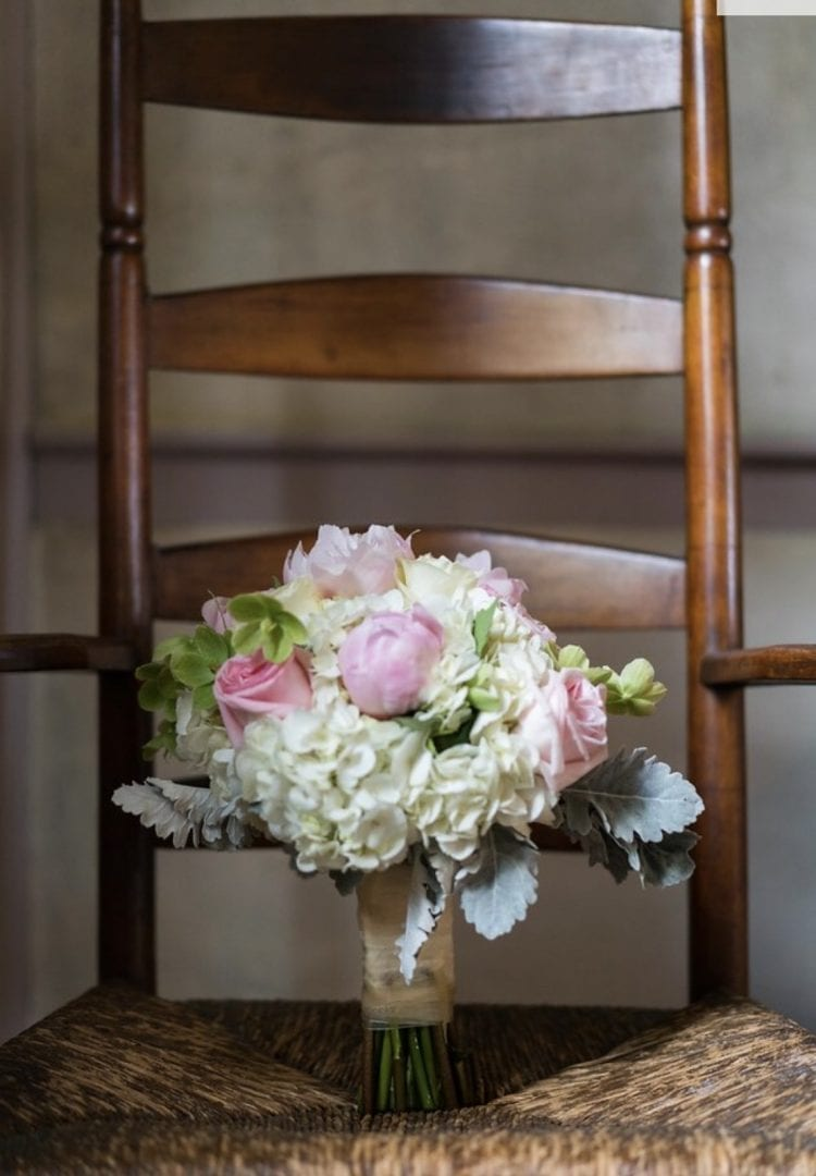 A wedding bouquet with white and pink flowers sits atop a brown chair.